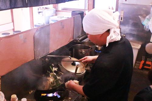 鍋をあおる佐久名さんの画像