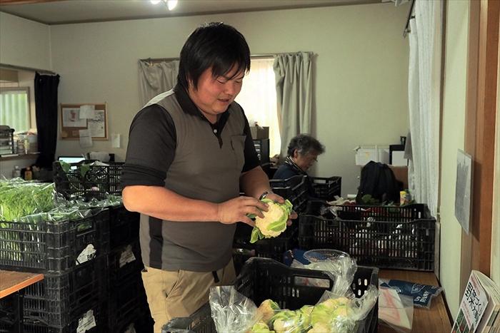 収穫した野菜の袋詰めをする渡辺さん